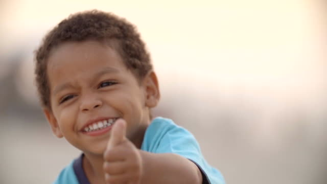 Cute Brazilian boy gives thumbs up and smiles for camera on Copacabana Beach