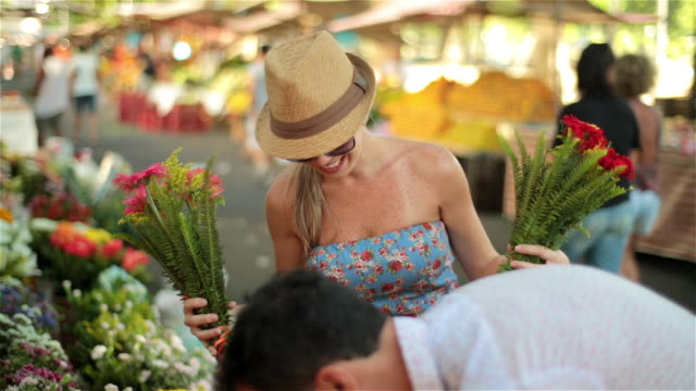 Cute Brazilian girl poses with colorful bouquets of flowers as boyfriend picks them out in sunny Rio market