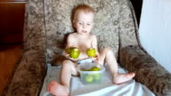 cute child eating pears in armchair