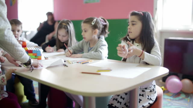 Cute children playing and writing in the classroom