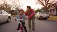 WS SLO MO. Cute girl learns to ride bicycle on neighborhood street as dad runs alongside.
