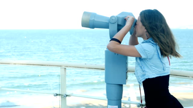 Cute girl looking at the sea through coin operated spy glass or public binoculars