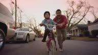 WS SLO MO. Cute girl pedals pink bicycle and smiles at camera as dad runs alongside.