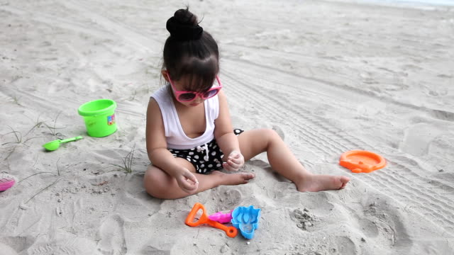 Cute girl playing sand on the beach
