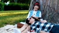 Cute girl reading a book while her boyfriend eat a cherry