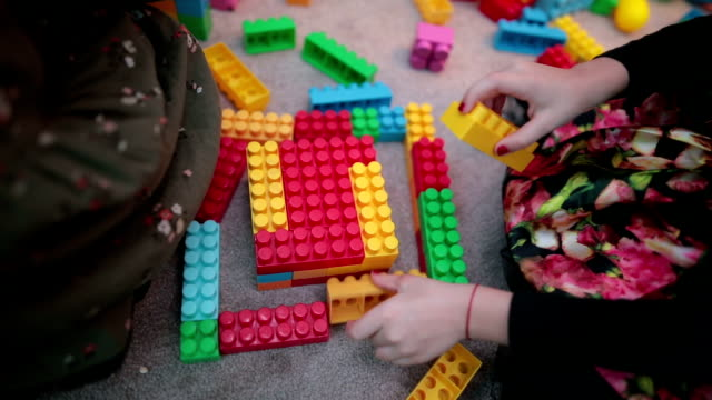 Cute girls in kindergarten playing with toy blocks