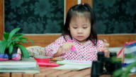 Cute Little Asian Girl Drawing a Picture on Desk