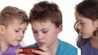 cute little boy (seven-years-old) playing with smartphone - two friends watching him
