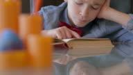 Süße kleine Junge liest ein Buch