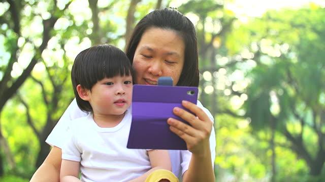 4K: schattige kleine jongen zitten met zijn moeder en spelen met mobiele telefoon in een park. Schieten op moment van de avond met mooie zonlicht.