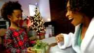 Cute little girl gives present to mom on Christmas morning
