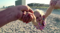 Cute little girl laughs as dad swings her around on sunny beach