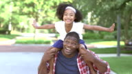 Cute little mixed race girl on father's shoulders