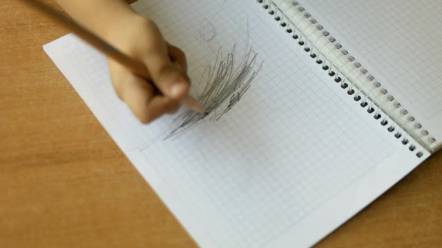 Cute pupil writing at desk