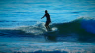 A cute surfer girl catches an ocean wave and rides it with grace and poise, showcasing femininity but with an edge of athleticism and grace.