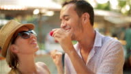 Cute young couple share a strawberry at Brazilian outdoor market