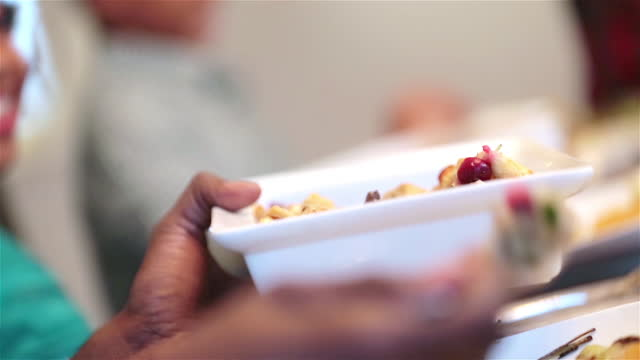 Cute young girl helps pass plates of food around table for Christmas dinner, father serves himself casserole