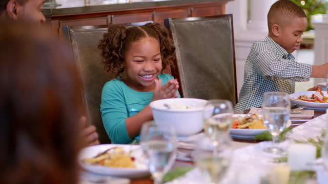 Cute young girl rubs hands together and gazes hungrily at the mashed potatoes (dolly-shot)