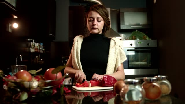 Cute young woman slicing cutting red pepper on the kitchen counter