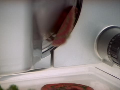 Cuting salami sausage with machine