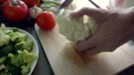 cutting a cauliflower on a wooden board