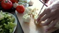cutting a cauliflower on a wooden board.