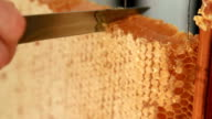 cutting a piece of scented honeycomb, concept of healthy eating