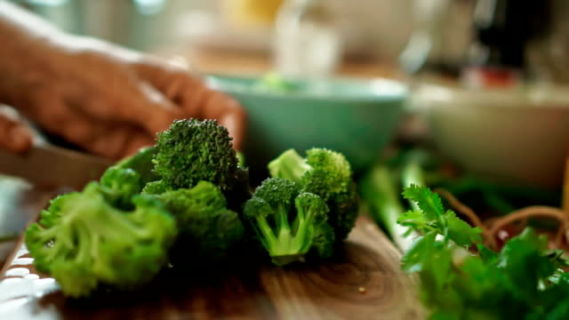 Cutting Broccoli on a cutting board for Nasi Goreng