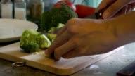 Cutting Broccoli on a cutting board.