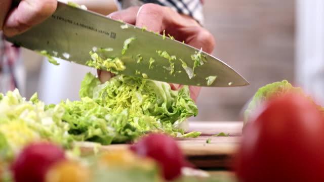 Snijdende frisse groene salade voor het voorbereiden van de salade