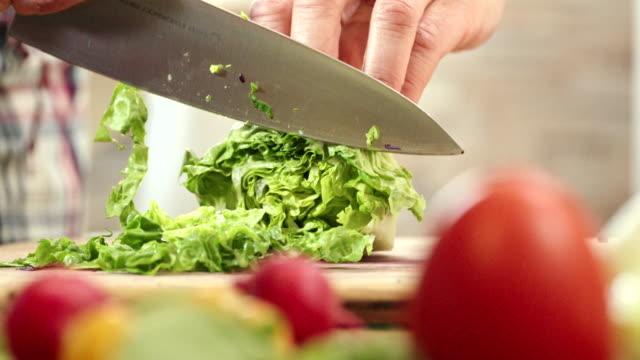 Snijdende verse groenten voor het voorbereiden van de salade