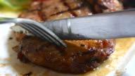 Cutting grilled piece of steak, 4K(UHD)