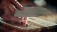 Schneiden roten Chilischoten mit Messer auf Küche Bord
