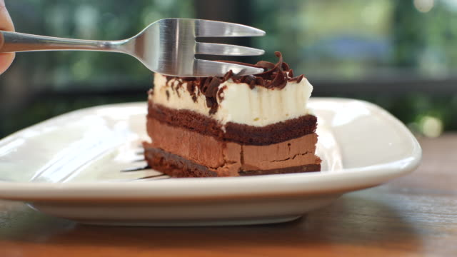 cutting slice of cake with chocolate dressing