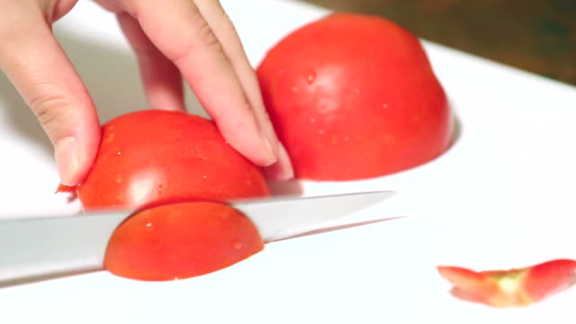 Cutting tomatoes close up.