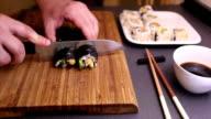 Cutting vegetarian futomaki sushi roll