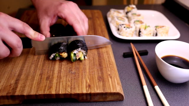 Cutting vegetarian futomaki sushi roll