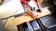 Cutting wood on a circular saw machine.