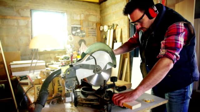 Cutting wood on a circular saw machine.