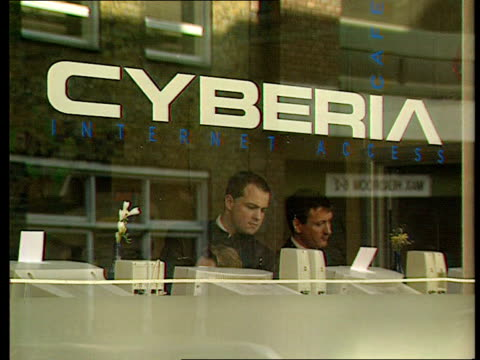 GV 'Cyberia' sign on window of internet cafe GBV People sitting at computers in internet cafe