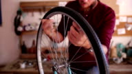 Cycle mechanic repairs the wheel of a bicycle.