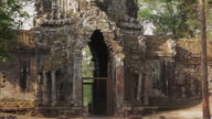 MS, TU A cyclist and motorcycle pass through Angkor Thom North Gate in Angkor Wat / Siem Reap, Cambodia