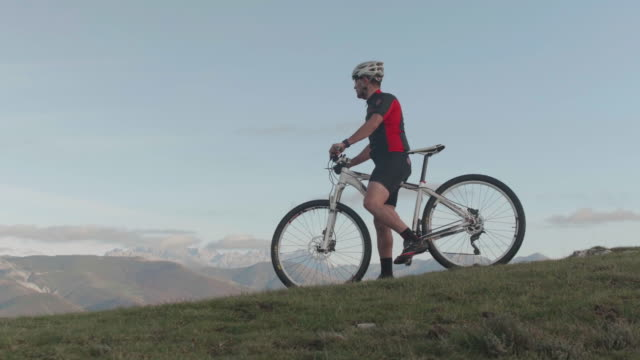 Cyclist with mountain bike in the hill stops the bike and looks at the landscape and continues riding
