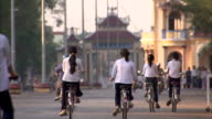 Cyclists and motorcyclists ride towards Cao Dai Temple.