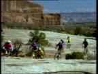 Cyclists racing along cliff-top heading towards camera