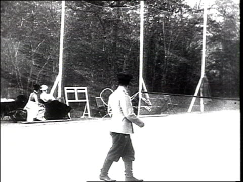Czar Nicholas II plays tennis w/ relatives while having holidays in the Gulf of Finland WS of tennis court two ladies watch the game vs of men in...