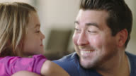CU. Dad plays acoustic guitar for his daughter as she leans on his shoulder and gazes at him with a smile.
