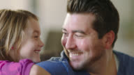 CU. Dad strums acoustic guitar and laughs with his daughter as she leans on his shoulder.