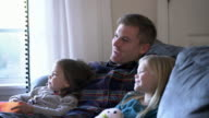 MS Dad watching TV with his daughters