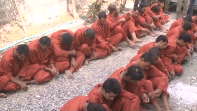 Daesh terrorists wearing orange suits captured by peshmerga are seen in Kirkuk Iraq on September 14 2015 Peshmerga forces captured 45 Daesh...